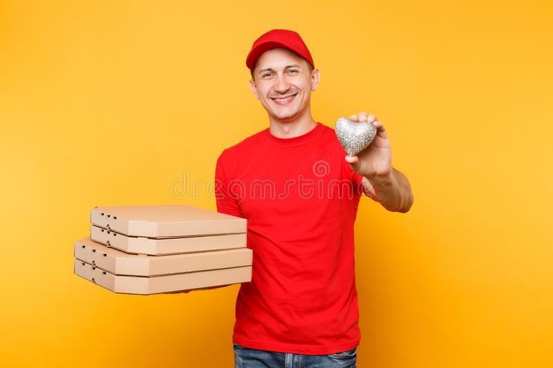 Delivery man in red cap t-shirt giving food order pizza boxes isolated on yellow background. Male employee pizzaman. Delivery man in cap t-shirt giving food stock image