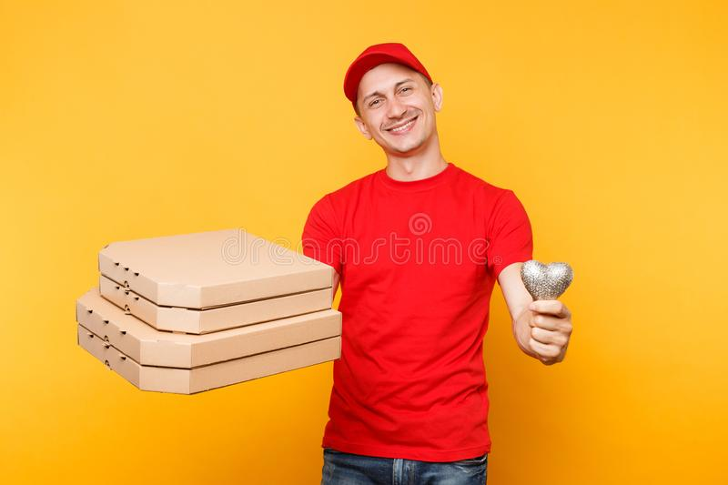 Delivery man in red cap t-shirt giving food order pizza boxes isolated on yellow background. Male employee pizzaman. Delivery man in cap t-shirt giving food stock images