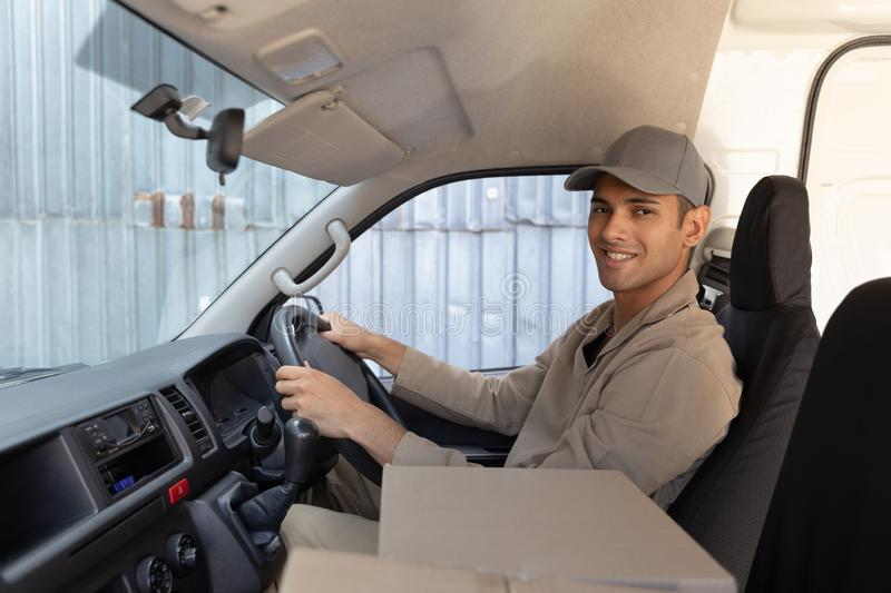 Delivery man with cardboard boxes sitting in front seat of car outside the warehouse. Side view of delivery man with cardboard boxes sitting in front seat of car stock images