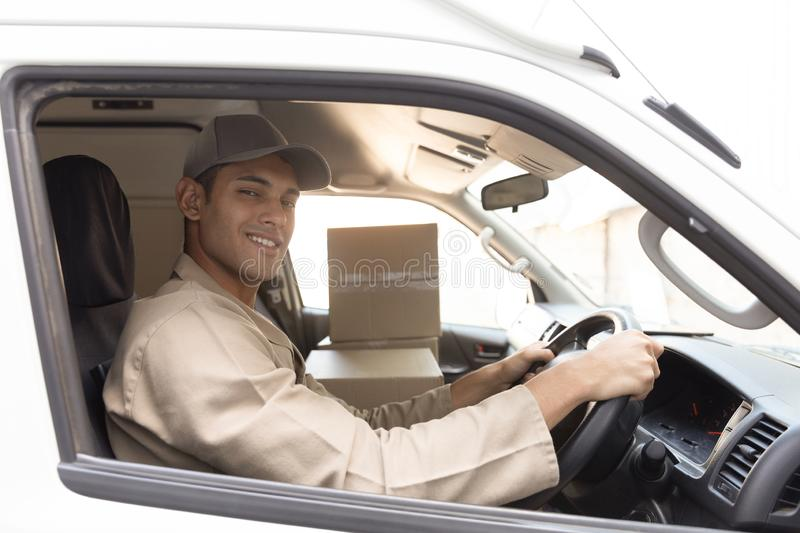 Delivery man with cardboard boxes sitting in front seat of car outside the warehouse. Side view of delivery man with cardboard boxes sitting in front seat of car stock photo