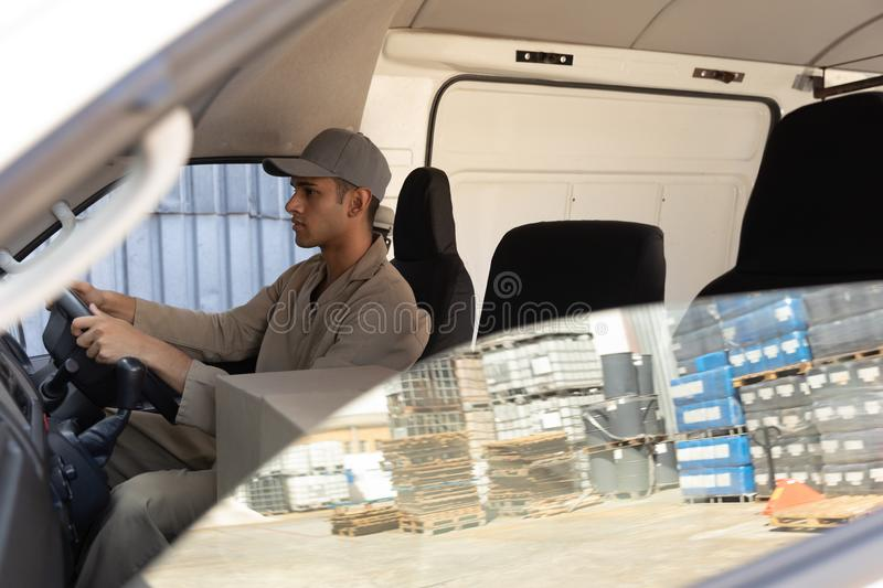 Delivery man with cardboard boxes sitting in front seat of car outside the warehouse. Side view of delivery man with cardboard boxes sitting in front seat of car royalty free stock photos