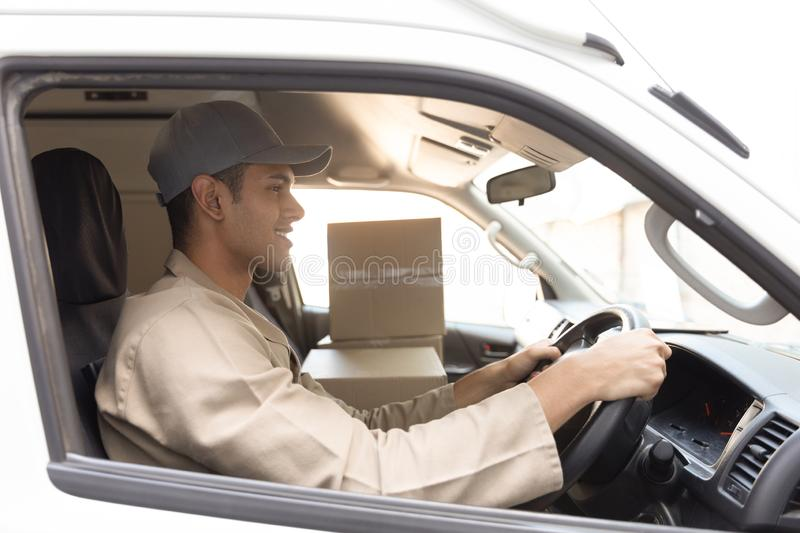 Delivery man with cardboard boxes sitting in front seat of car outside the warehouse. Side view of delivery man with cardboard boxes sitting in front seat of car royalty free stock image