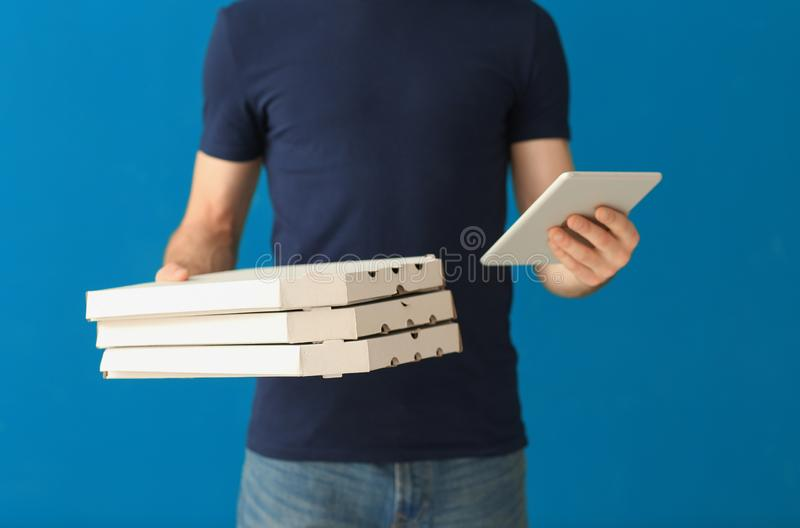 Delivery man with cardboard pizza boxes and tablet on color background stock photography