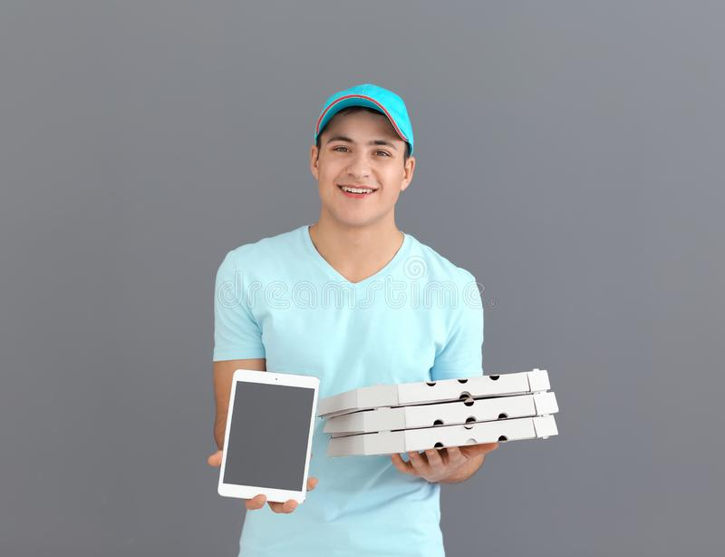 Delivery man with cardboard pizza boxes and tablet on grey background royalty free stock photos