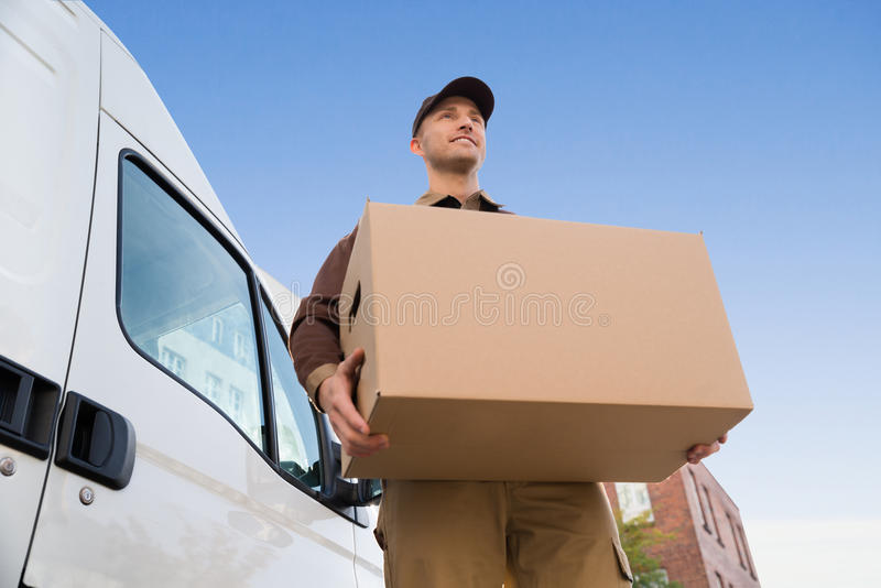 Delivery Man Carrying Cardboard Box By Truck Against Sky. Low angle portrait of young delivery man carrying cardboard box by truck against sky stock photos