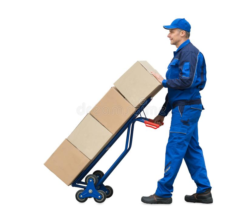 Delivery Man Carrying Cardboard Boxes On Hand Truck. Mature Delivery Man Carrying Cardboard Boxes On Hand Truck Over White Background royalty free stock photos