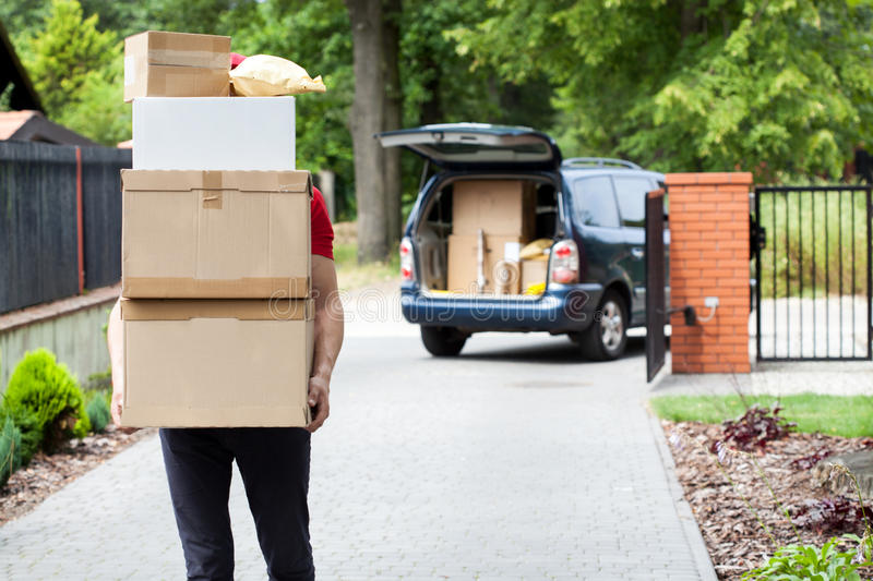 Delivery man carrying package stack. Delivery guy carrying a stack of parcels from his van royalty free stock images