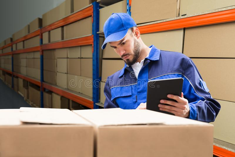 Delivery Man Checking His Package On Digital Tablet royalty free stock images