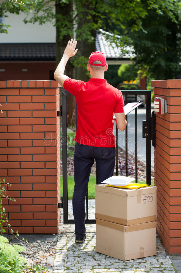 Delivery man delivering packages to home. Vertical royalty free stock photos