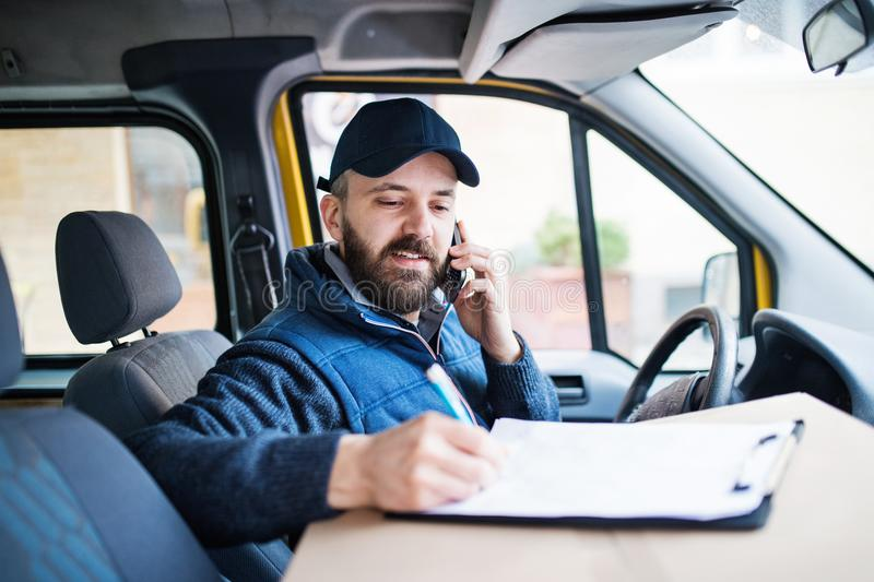 Delivery man delivering parcel box to recipient. stock images