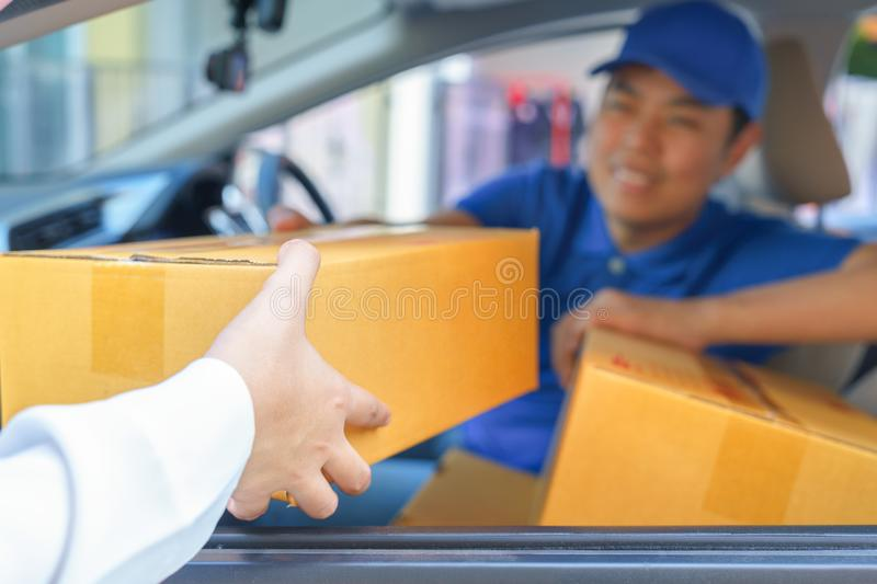 Delivery man giving a package box to customer while sitting in c. Ar royalty free stock photography