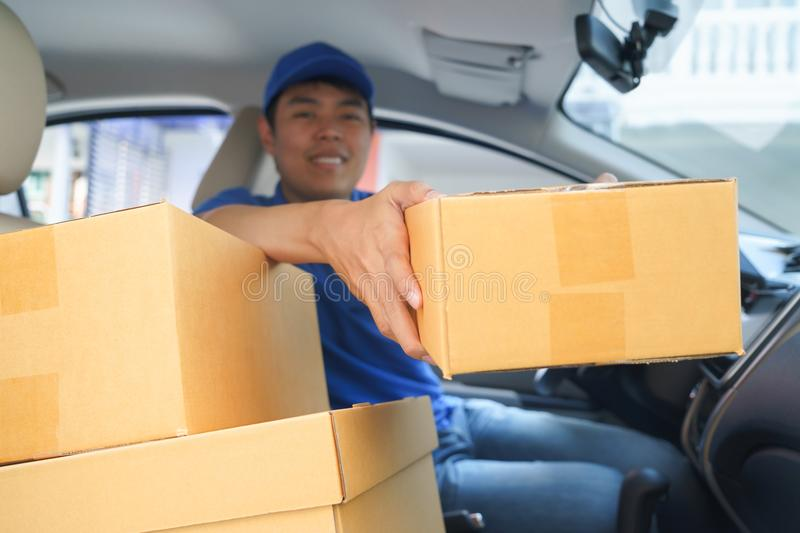 Delivery man giving a package box to customer while sitting in c. Ar royalty free stock photo