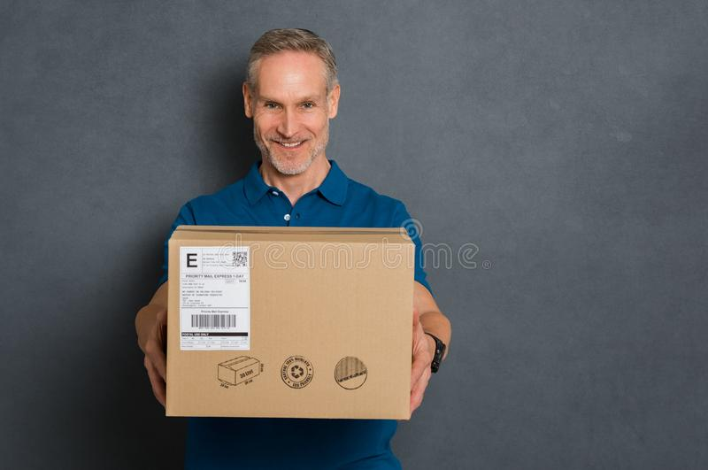 Delivery man giving package. Happy delivery man stretching out his arms to give the package. Smiling courier giving card box on grey background. Portrait of stock photos