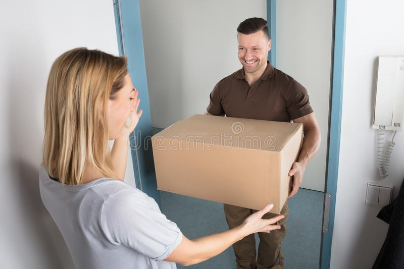 Delivery Man Giving Parcel Box To Young Woman stock image