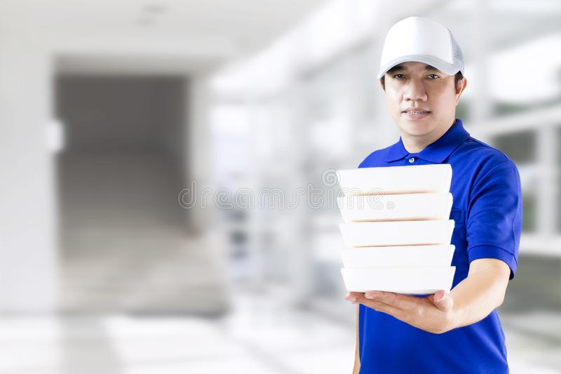 Delivery man hand holding fast food packaging in blue uniform. Food delivery service or order food online concept. Business and. Technology for lifestyle in royalty free stock photos
