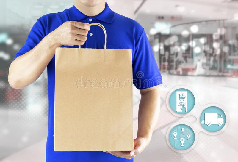 Delivery man hand holding paper bag in blue uniform and icon media for order shopping online. Delivery service delivering package stock images