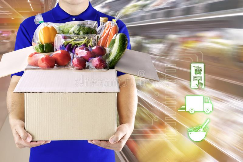 Delivery man hand holding paper box package in blue uniform and icon media symbol on grocery background. Delivery service. Ingredients food for order online royalty free stock image