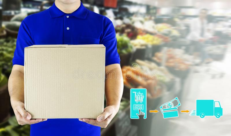 Delivery man hand holding paper box package in blue uniform and icon media symbol on grocery background. Delivery service. Ingredients food for order online stock image