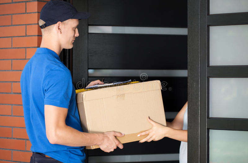 Delivery man handing in parcel. Woman receiving a parcel from a delivery huy stock photo