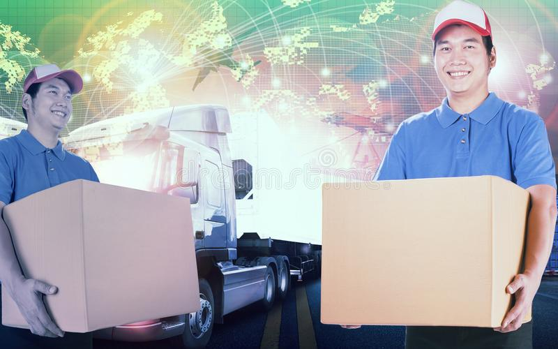 delivery man holding card box standing against logistic background royalty free stock photography