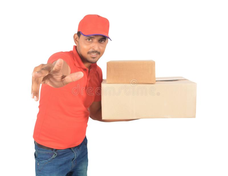 Delivery man holding carton boxes, pointing at in uniform stock photography