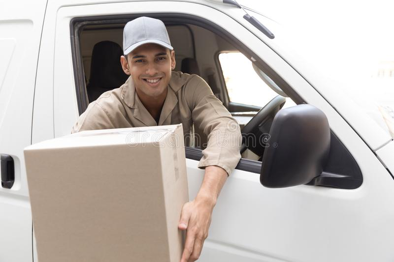 Delivery man holding a package while sitting in van outside the warehouse. Happy delivery man holding a package while sitting in van outside the warehouse. This stock photography