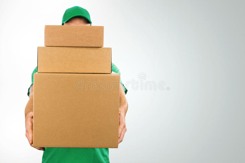 Delivery man holding pile of cardboard boxes in front stock photography