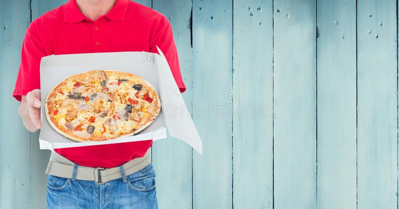 Delivery man holding pizza box against wooden background royalty free stock photos