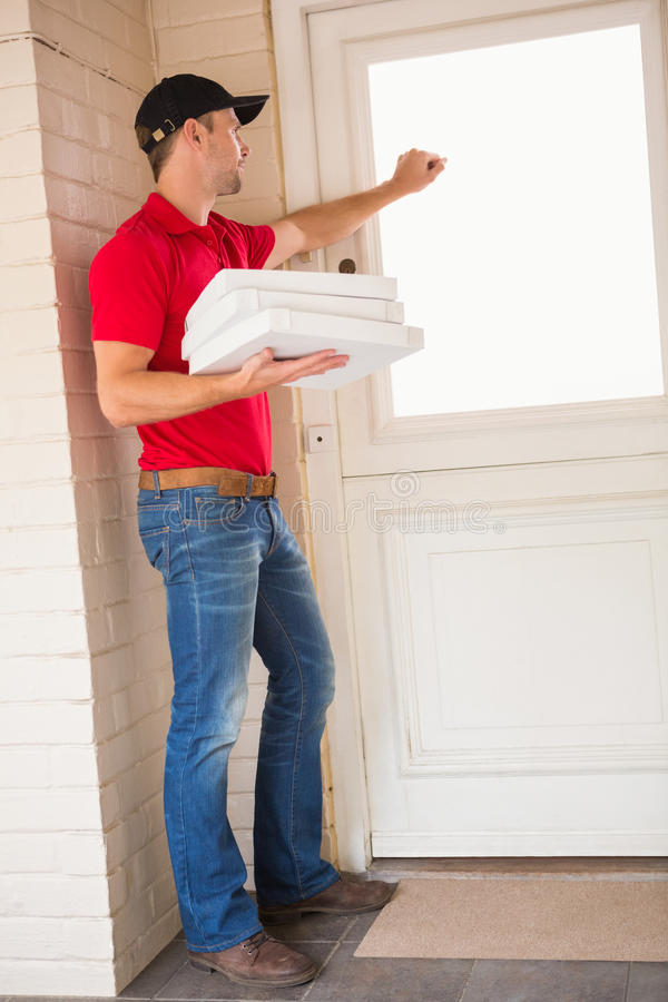 Download Delivery Man Holding Pizza While Knocking On The Door Stock Photo - Image 47017602 & Delivery Man Holding Pizza While Knocking On The Door Stock Photo ...
