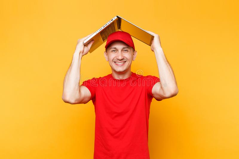 Delivery man isolated on yellow orange background. Professional male employee courier in red cap, t-shirt holding above. Head like roof laptop pc computer royalty free stock photo