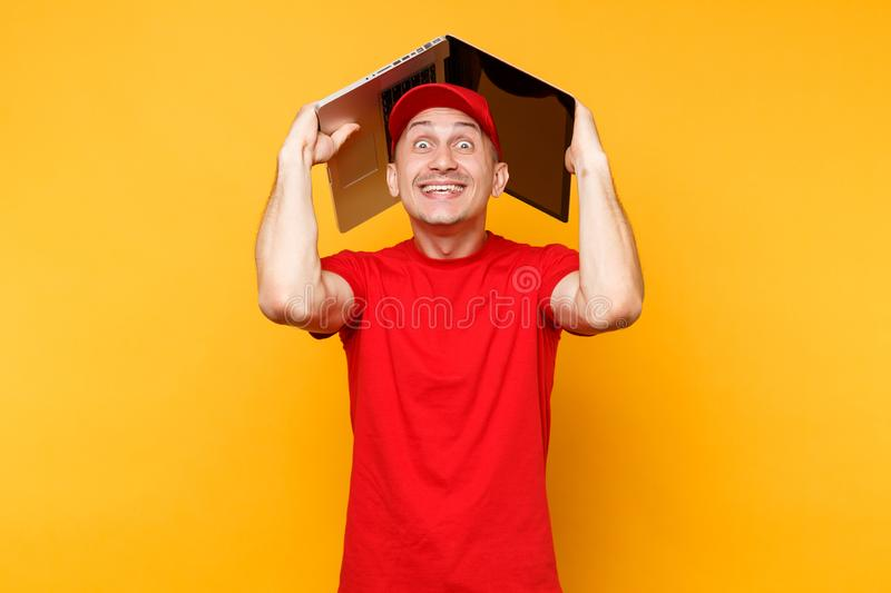 Delivery man isolated on yellow orange background. Professional male employee courier in red cap, t-shirt holding above. Head like roof laptop pc computer royalty free stock images