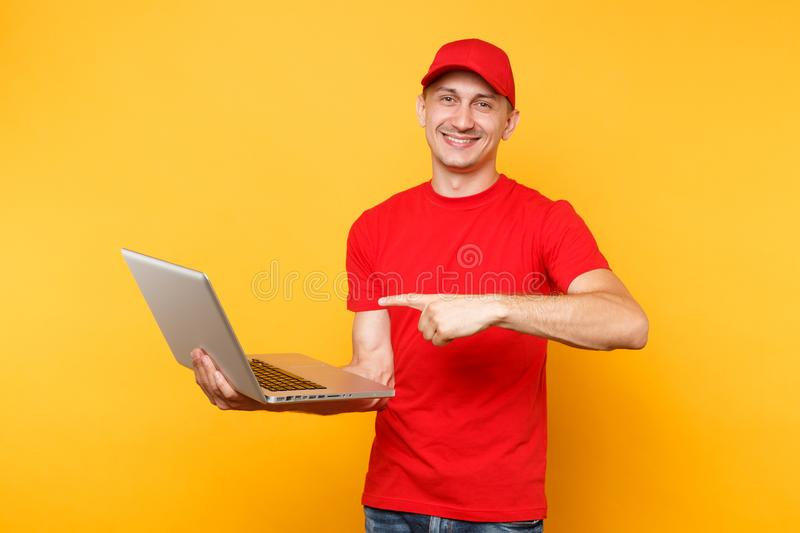 Delivery man isolated on yellow orange background. Professional male employee courier in red cap, t-shirt holding. Working typing on laptop pc computer. Service stock photos