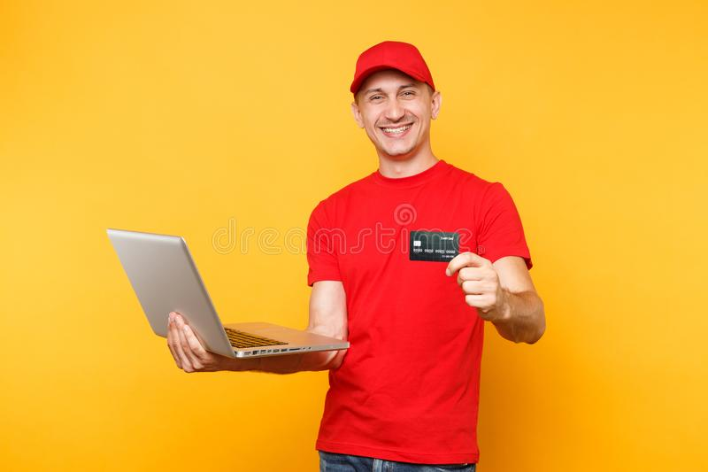 Delivery man isolated on yellow orange background. Professional male employee courier in red cap, t-shirt holding laptop. Pc computer, credit bank card. Service stock image