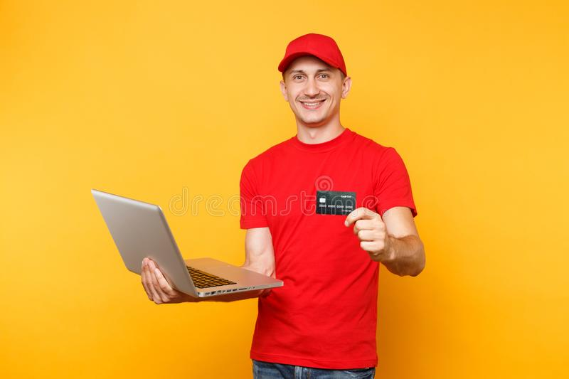 Delivery man isolated on yellow orange background. Professional male employee courier in red cap, t-shirt holding laptop. Pc computer, credit bank card. Service stock photography