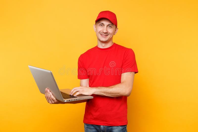 Delivery man isolated on yellow orange background. Professional male employee courier in red cap, t-shirt holding. Working typing on laptop pc computer. Service royalty free stock photography
