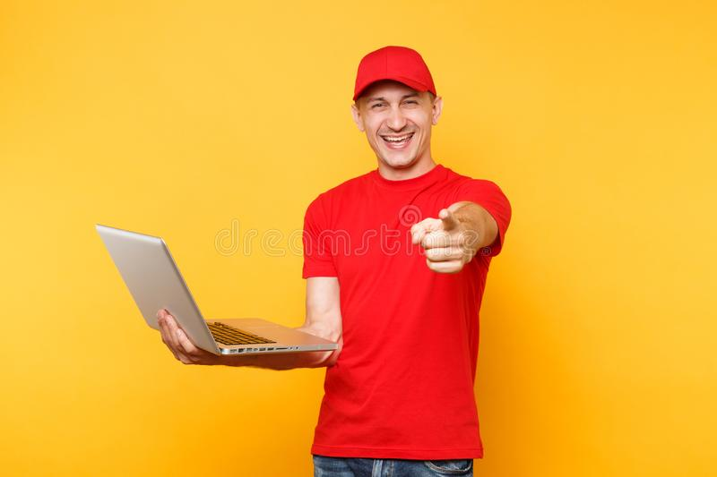 Delivery man isolated on yellow orange background. Professional male employee courier in red cap, t-shirt holding. Working typing on laptop pc computer. Service royalty free stock images