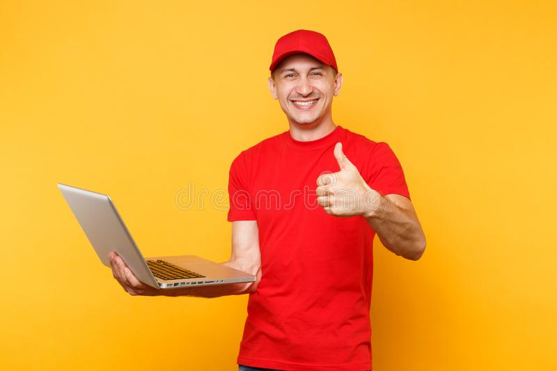Delivery man isolated on yellow orange background. Professional male employee courier in red cap, t-shirt holding. Working typing on laptop pc computer. Service royalty free stock photo