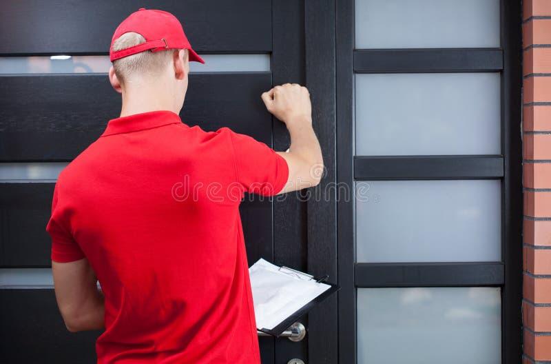 Delivery man knocking on the client's door. Back view of a delivery man knocking on the client's door stock image
