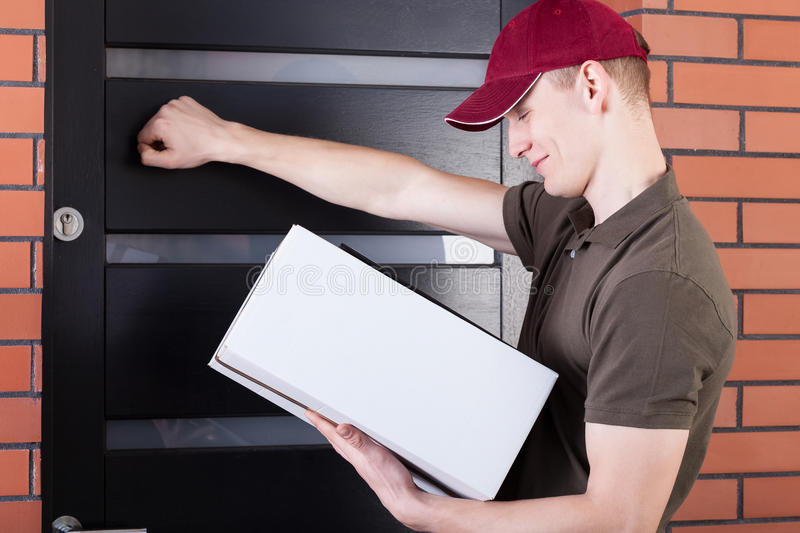 Delivery man knocking on the door. Young delivery man knocking on the client door stock photos