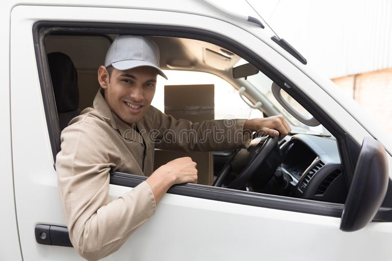 Delivery man looking at camera while sitting in front seat of car outside the warehouse. Side view of delivery man looking at camera while sitting in front seat stock images