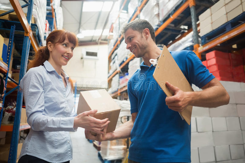 Delivery man passing parcel to warehouse manager. Delivery men passing parcel to warehouse manager in warehouse stock images
