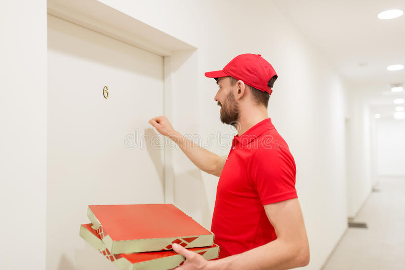 Delivery man with pizza boxes knocking on door. Food delivery, mail and people concept - man delivering pizza in paper boxes to customer home and knocking on stock photography