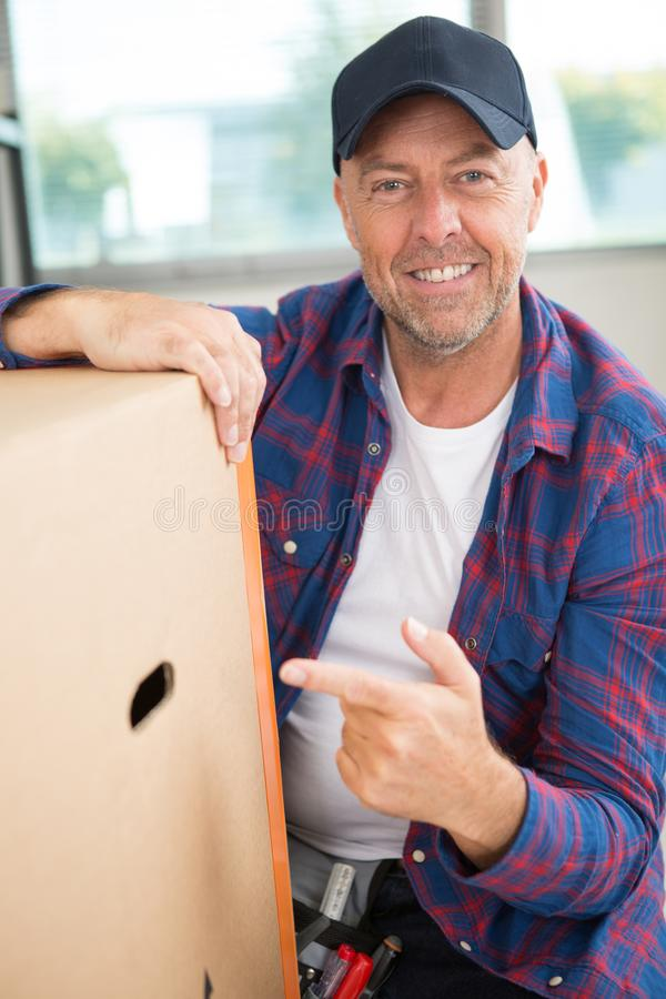 Delivery man pointing cardbox stock photos