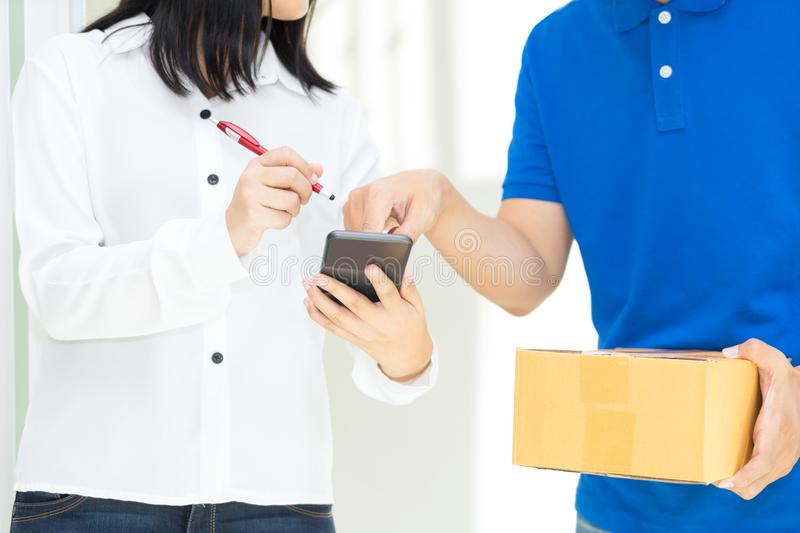 Delivery man pointing on smartphone and woman receiving package. Delivery men pointing on smartphone and women receiving package and signing on digital mobile royalty free stock photo