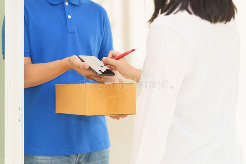 Delivery man pointing on smartphone and woman receiving package. And signing on digital mobile phone stock image