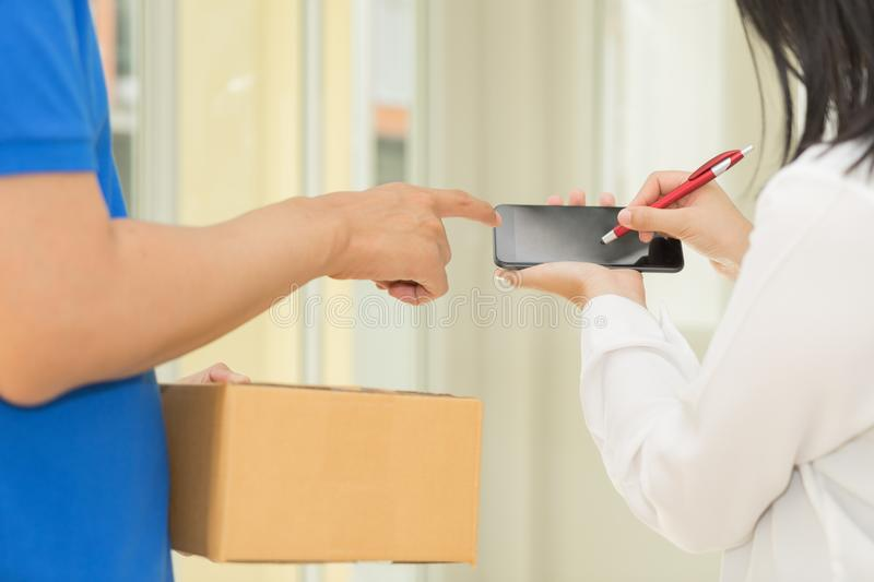 Delivery man pointing on smartphone and woman receiving package. And signing on digital mobile phone stock photo