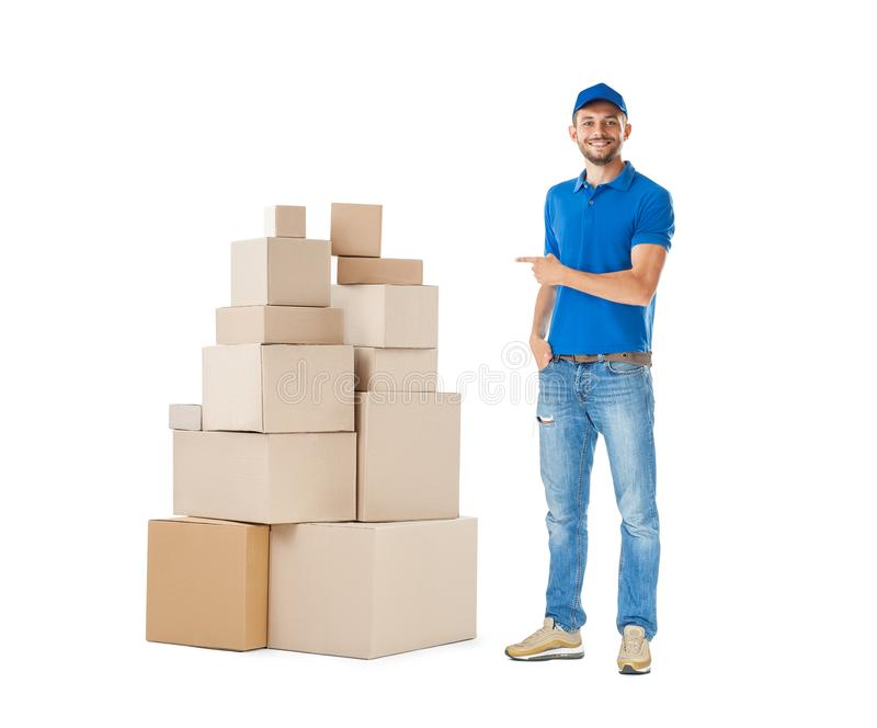 Delivery man pointing to stack of boxes isolated on white background royalty free stock photos