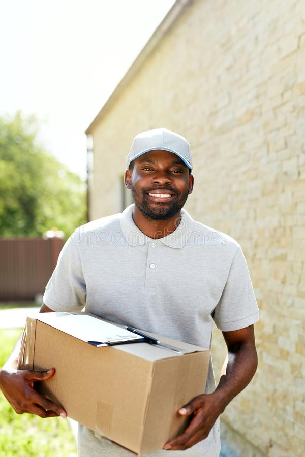 Delivery Man. Portrait Of Smiling Courier With Box Package. In Uniform Outdoors. High Resolution stock photography