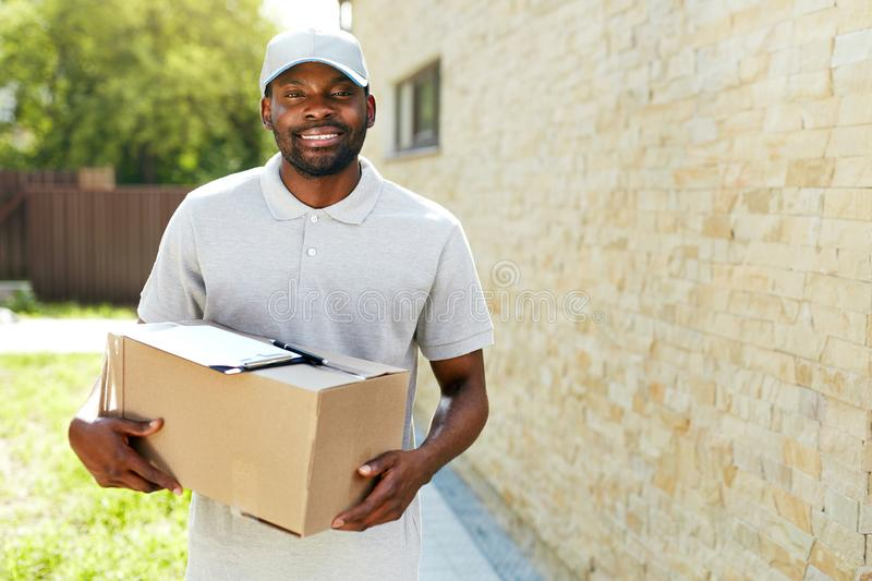 Delivery Man. Portrait Of Smiling Courier With Box Package stock photography