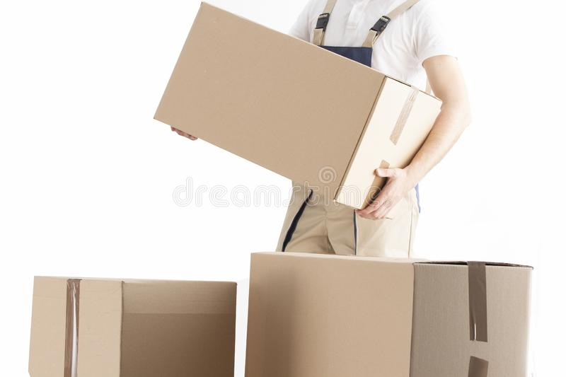 Delivery man puts cardboard box. Relocation service concept. Loader with box. Mover in uniform. stock image